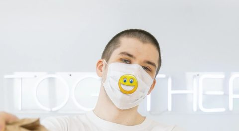 man wearing mask with happy face on it